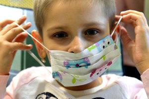 Na snímke deti si nasadzujú veselé rúška.