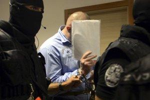 Kukláči privádzajú jedného z obžalovaných.