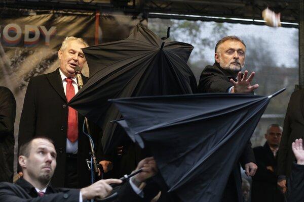 Členovia ochranky dáždnikmi chránia českého prezidenta Miloša Zemana.