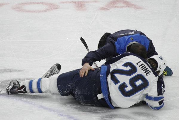 Patrik Laine zostáva ležať na ľade po zákroku Jakea McCabea.