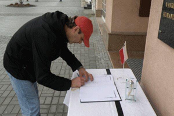 Ľudia podpisujú kondolenčnú listinu pred Mestským domom v Prievidzi.