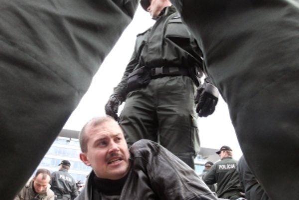"""Zadržiavanie Mariána Kotlebu počas zhromaždenia nacionalistov v Bratislave po tom, čo do mikrofónu zakričal pozdrav """"Na stráž""""."""