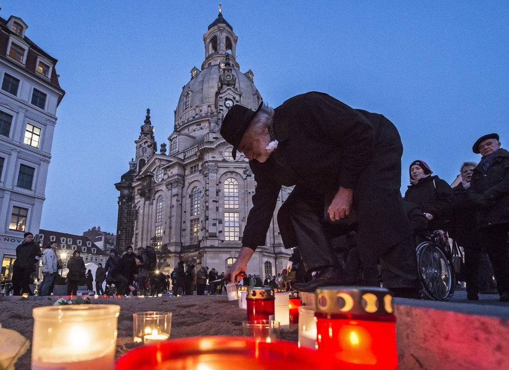 Muž zapaľuje sviečku na námestí pred chrámom Frauenkirche v nemeckých Drážďanoch.