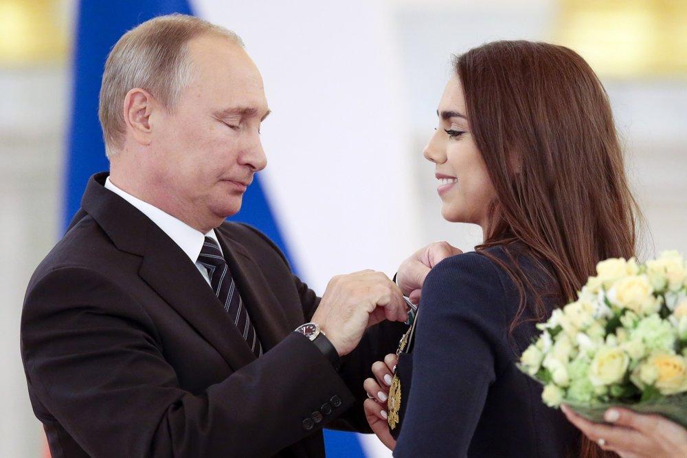 Ruský prezident Vladimir Putin pripína vyznamenanie zlatej medailistke, ruskej atlétke v modernej gymnastike Margarite Mamunovej počas odovzdávania vyznamenaní pre členov ruskej olympijskej výpravy po ich príchode z OH 2016 v Rio de Janeiro 25. augusta 2016.
