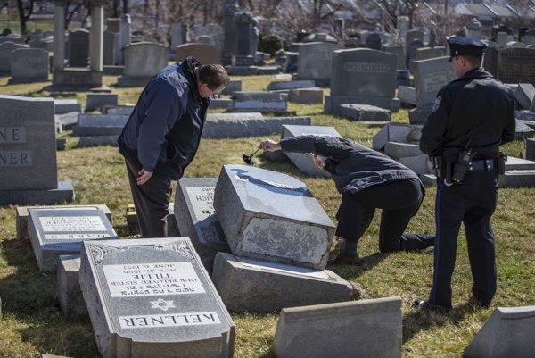 Policajti odoberajú odtlačky prstov na jednom z mnohých poškodených náhrobných kameňov na židovskom cintoríne vo Filadlfii.