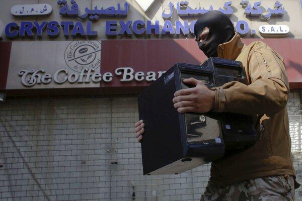 Libanonský policajt nesie počítače zhabané počas razie.
