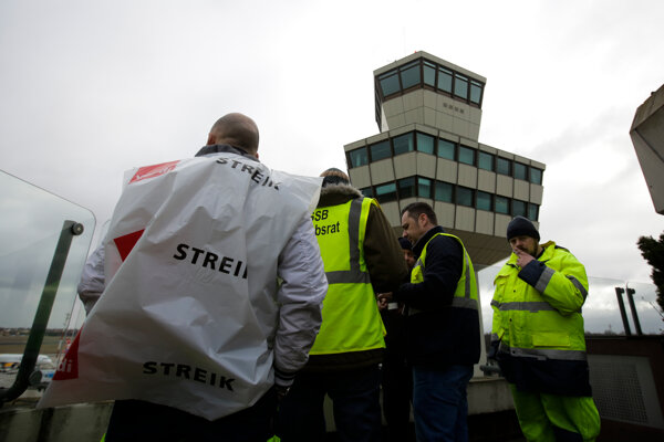pracovníci pozemného personálu stoje pri veži na hlavnom letisku Tegel počas štrajku v Berlíne.