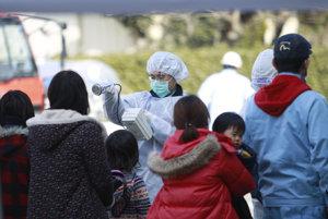Na archívnej snímke z 13. marca 2011 kontrolujú vystavenie žiareniu u obyvateľov mesta Korijama v prefektúreFukušima.