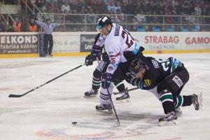 Dvaja hráči Nových Zámkov sa pokúšajú odstaviť od puku Michala Handzuša (v bielom).