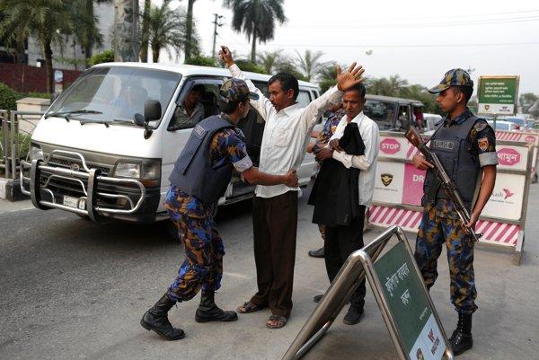 Polícia na letisku v Dháke prehliada pasažierov.