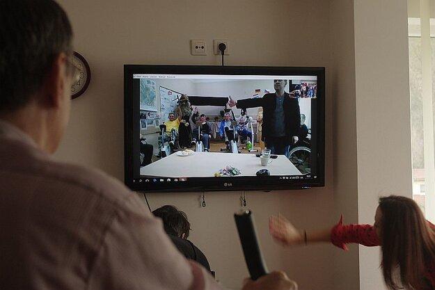 Na monitore sledujú výkony iných seniorov.