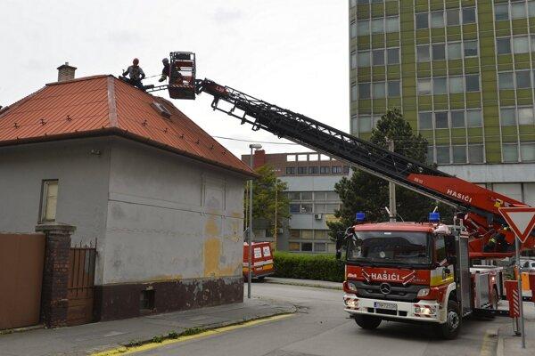 Na snímke hasiči opravujú plechovú strechu na dome, ktorú poškodil silný nárazový vietor na Jilemnického ulici v Trenčíne.