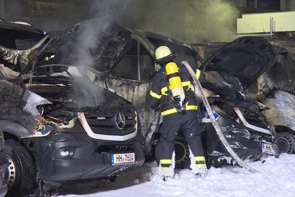 Na snímke hasič sa snaží uhasiť horiace policajné vozidlá 27. marca 2017 v Hamburgu.