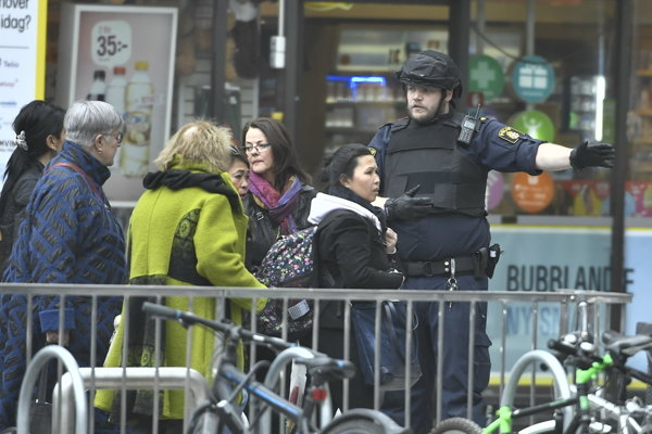 Na snímke policajt usmerňuje chodcov po útoku kamióna, ktorý vrazil do davu ľudí v Štokholme.