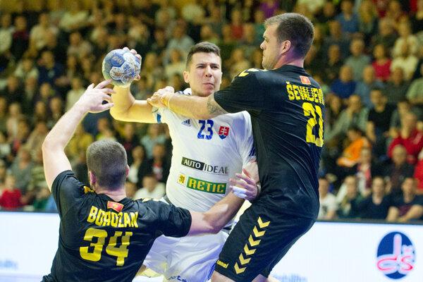 Na snímke z prvého zápasu, ktorý sa uskutočnil 3. mája v Hlohovci, sa márne pokúša dostať do zakončenia cez dvojicu brániacich hádzanárov Čiernej Hory Lukáš Urban.
