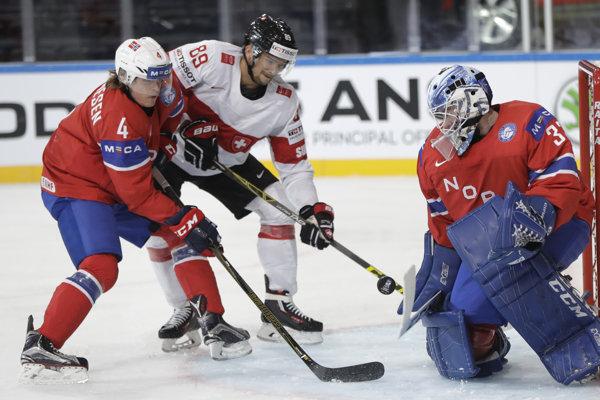 Pred nórskym brankárom Henrikom Haukelandom sa snaží presadiť Cody Almond, bráni ho Johannes Johannesen.