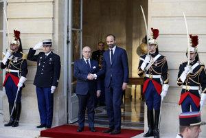 Nový premiér Edouard Philippe (v stredu vprav) si podáva ruku so svojim odchádzajúcim predchodcom Bernardom Cazeneuveom.