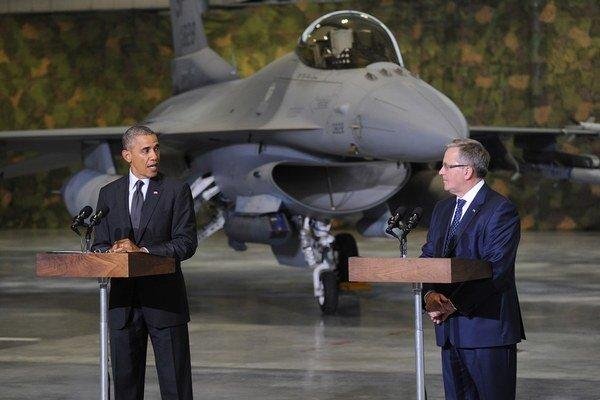 Obama (vľavo) pred novinárov predstúpil v hangári s americkou stíhačkou F16.