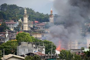 Dym stúpa z horiaci domov po leteckých útokov filipínskych vzdušných síl vo filipínskom meste Marawi.
