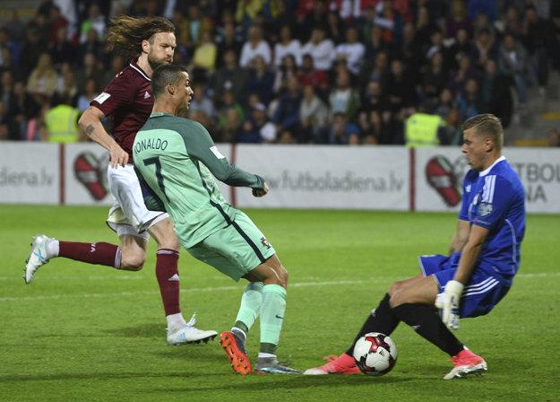Cristiano Ronaldo zakončuje v šanci pred brankárom Andrisom Vaninsom.