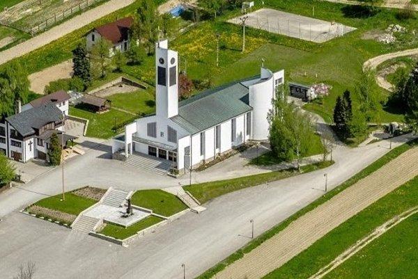 Jedna z dominánt Dediny roka - Oravskej Polhory - kostol, pred ktorým stojí socha svätého otca Jána Pavla II.