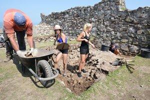 Čistenie kamenného bloku muriva s omietkami pri veži vo východnej línii opevnenia Horného hradu.
