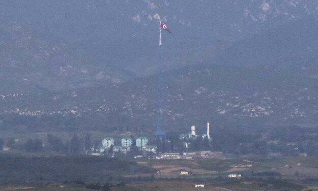 Pohľad cez hranice do Severnej Kórei. Stožiar s vlajkou KĽDR meria približne 160 metrov.
