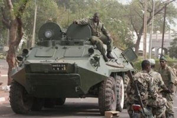 Vojaci hliadkujú neďaleko prezidentského paláca po vojenskom prevrate.