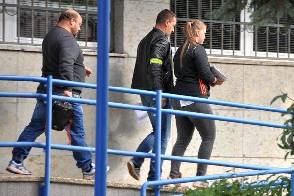 Veronika opúšťa budovu súdu v sprievode policajtov.