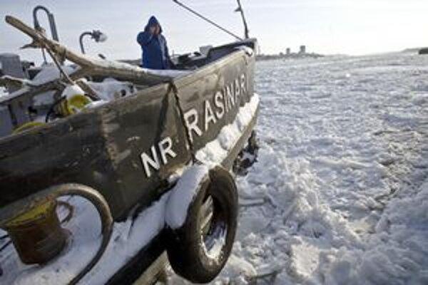 Muž na palube riečnej lode telefonuje po tom, čo jeho plavidlo uviazlo v ľadových kryhách.