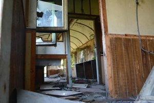 Interiér vagóna. Vegetácia sa tlačí do vnútra vozňa cez poškodené okná.