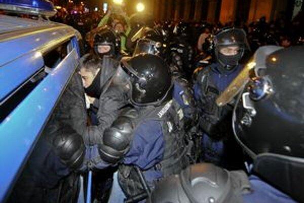 Policajti dávajú do dodávky zatknutého demonštranta v centre Bukurešti.