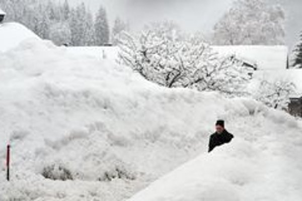 Muž kráča okolo kopy odhrnutého snehu pri ceste v Loferi v provincii Salzburg.