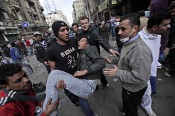 Zraneného demonštranta odnášajú do nemocnice.