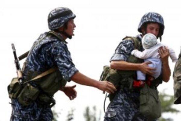 Kirgizskí vojaci si podávajú bábätko, keď usmerňujú dav etnických Uzbekov, čakajúcich na prechod cez hranice do Uzbekistanu 14. júna 2010 v juhokirgizskjom meste Oš. Pre násilie v južnom Kirgizsku  utiekli z krajiny tisícky etnických Uzbekov.