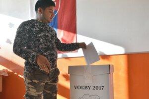 Na snímke volič s hlasovacími lístkami počas volieb do orgánov samosprávnych krajov v rómskej osade v Trebišove