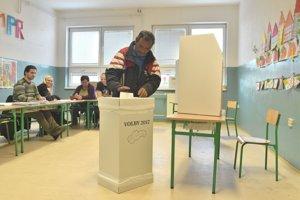Na snímke volič vhadzuje obálku s hlasovacími lístkami do volebnej schránky počas volieb do orgánov samosprávnych krajov v rómskej osade v Trebišove.