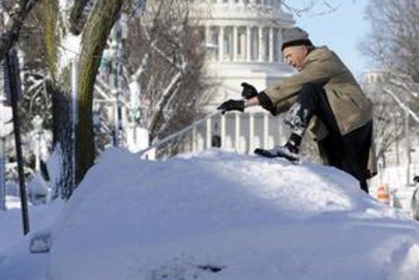 Obyvateľ Washingtonu metlou odpratáva sneh zo svojho auta zaviateho až po strechu.