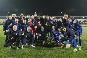 Slovenskí futbalisti sa spolu s realizačným tímom radujú z trofeje.