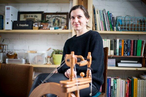 Ľubica Noemi Kováčiková pradie vlnu z quessantskej mini ovce na drevenom kolovrátku z Nového Zélandu.