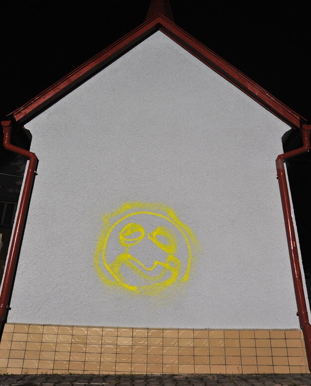 Na múre kaplnky je žltý výtvor neznámeho páchateľa.