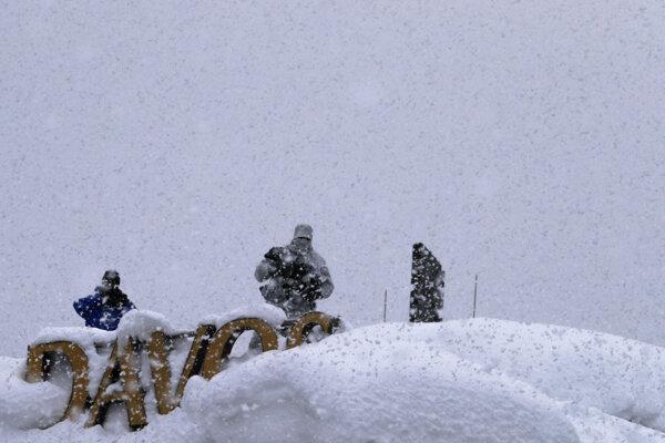 Policajti hliadkujú v zasneženom Davose pred začiatkom Svetového ekonomického fóra.