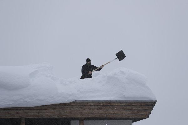 Policajt zhadzuje sneh z budovy hotela.