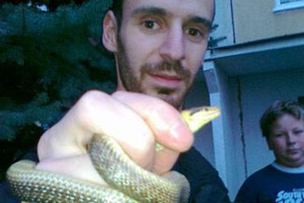 Mestský policajt s hadom, ktorého chytili v pivnici paneláku.