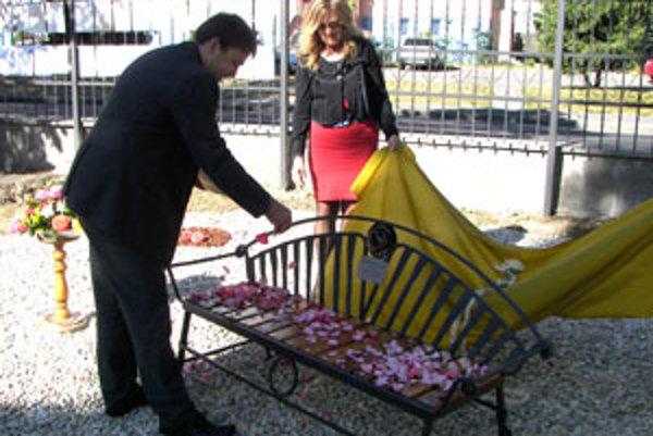 Primátor Radoslav Vazan posial lavičku lupeňmi ruží, pri jej odhalení mu asistovala riaditeľka centra Viera Kulichová.