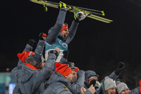 Arnd Peiffer oslavuje so svojimi krajanmi zisk zlatej olympijskej medaily.