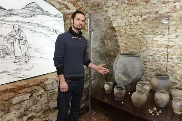 Peter Kočan, jeden z autorov výstavy ukazuje na najväčšiu nádobu výstavy, ktorou je zásobnica z 3. – 5. storočia z územia mesta Prešov.