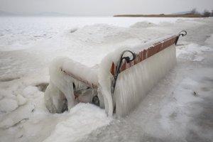 Ľad pokrýva lavičku a breh jazera Balaton v obci Balatonfenyves.