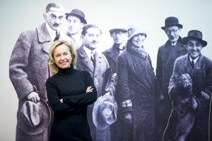 Kurátorka výstavy Henrieta Moravčíková pred fotografiou tímu architektonickej kancelárie Weinwurm a Vécsei v nadživotnej veľkosti. Friedrich Weinwurm je prvý zľava.