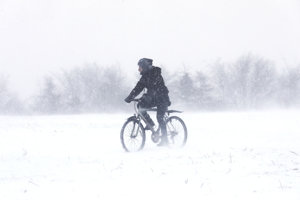 Cyklista odoláva snehovej búrke a silnému vetru v Helix parku v škótskom Falkirku.